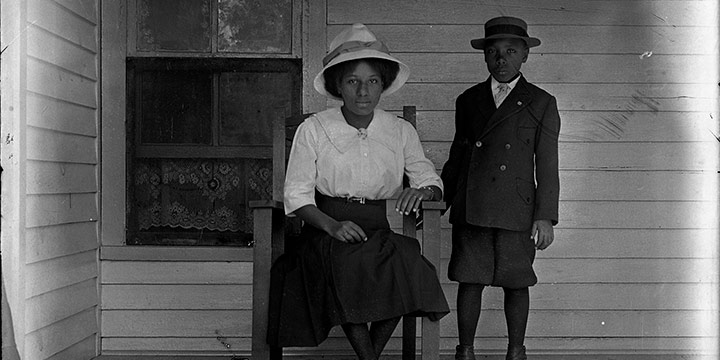 """John Johnson, Untitled (seated woman and boy on porch), black & white photograph (from glass plate negative in the MONA Archives Collection), 2018, 15¼ × 11"""""""